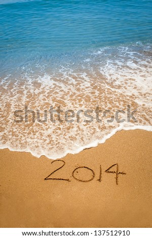 Year 2014 written in sand, on tropical beach - stock photo