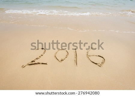 Year 2016 written in sand, on tropical beach - stock photo