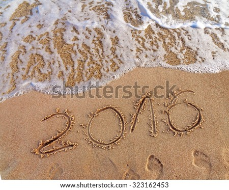 Year 2016 written in the sand and wave on a beach