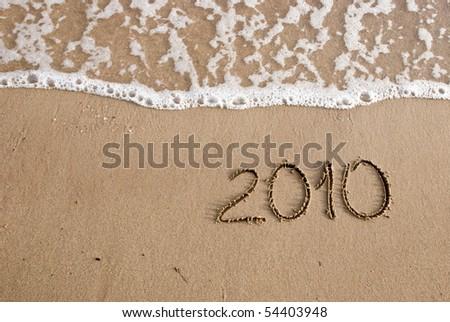 Year 2010 written on the sand - stock photo