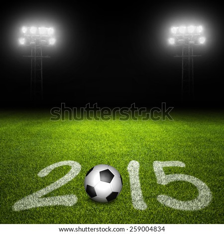 Year 2015 written with markings and ball on soccer field against illuminated stadium lights in background - stock photo