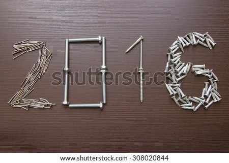Year written with metal nails and screws on wood background