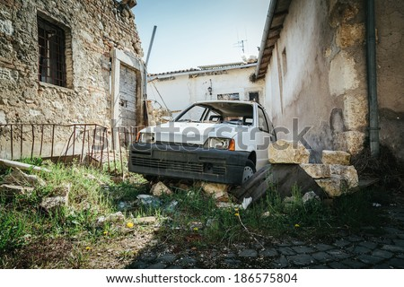 Years after the event of an earthquake, a car covered with rubble near the destroyed houses. - stock photo