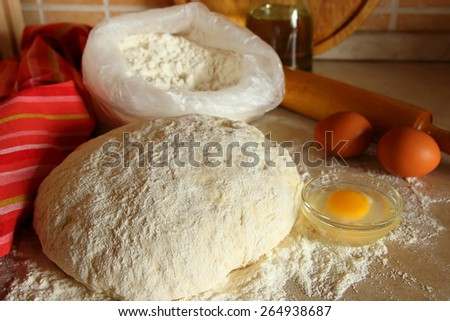 Yeast dough, eggs, and flour on the table