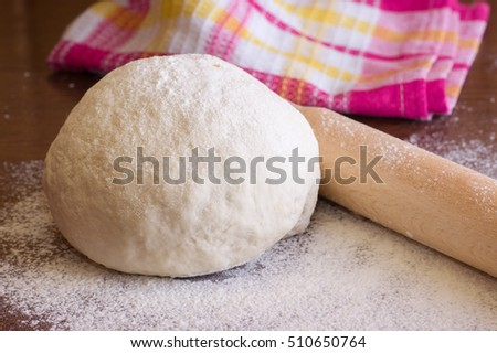 Yeast dough, flour, rolling pin on the wooden table