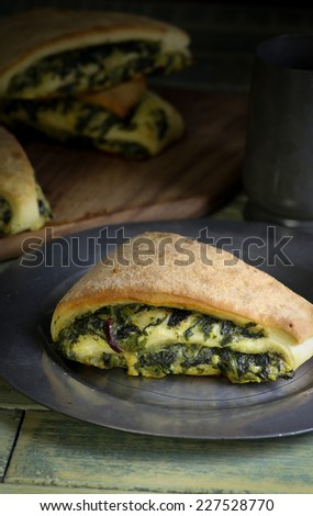Yeast dough rolls strudel with swiss chard and spinach and cheddar parmesan cheese - stock photo