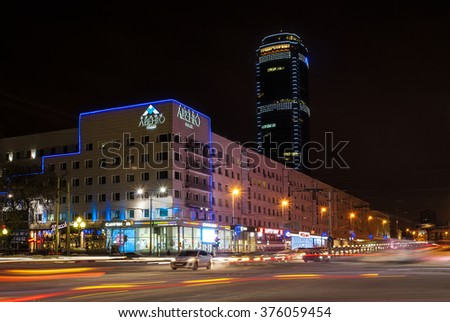 """Yekaterinburg, Russia - December 27, 2015: Night crossroad with blurred traffic. The photo shows the hotel building called the """"Avenue"""" and skyscraper """"Vysotsky"""" against the background. - stock photo"""