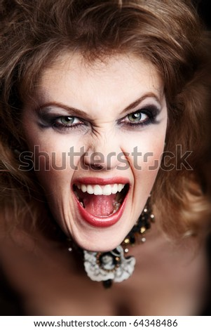 yelling woman with bright make-up on black background