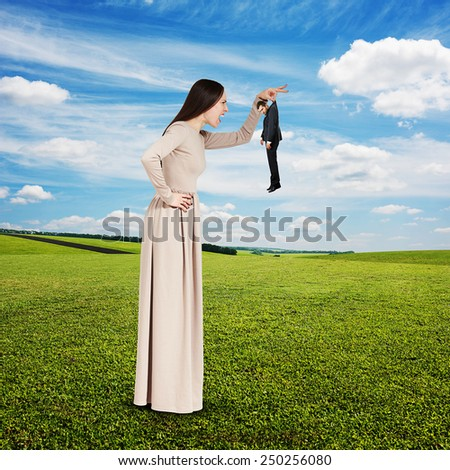 yelling young woman with small man over green field and blue sky - stock photo
