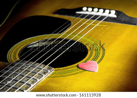 Yellow acoustic guitar with red pick