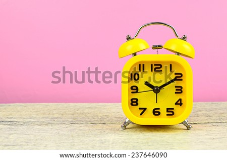 Yellow alarm clock on white wood table - stock photo