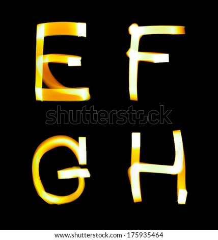 yellow alphabet created with light (E, F, G, H) - stock photo