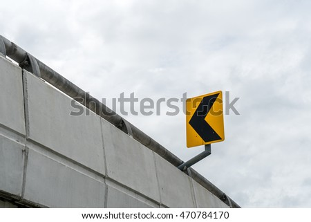 Yellow and black arrow traffic sign on express way