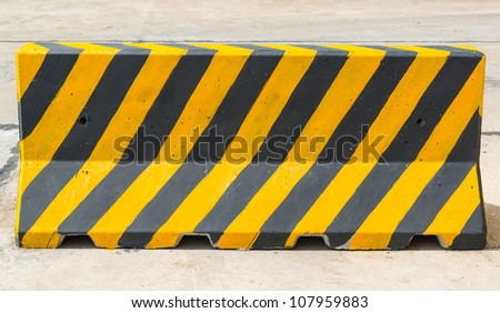 yellow and black concrete barriers blocking the road