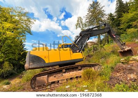 Yellow and Black Excavator Machine / Tracked excavator yellow and black at woods and blue sky with clouds - stock photo