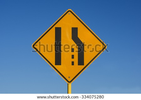 yellow and black right lane ends sign with blue sky background - stock photo