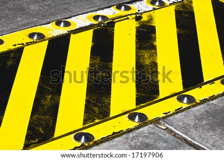 yellow and black striped speed bump - stock photo
