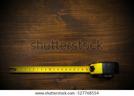 Yellow and black tape measure on a wooden and empty work table with dark shadows
