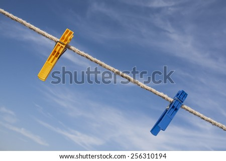 yellow and blue clothespins on a clothes line in front of a blue sky - stock photo