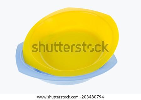 Yellow and blue plastic dish isolated on white background - stock photo