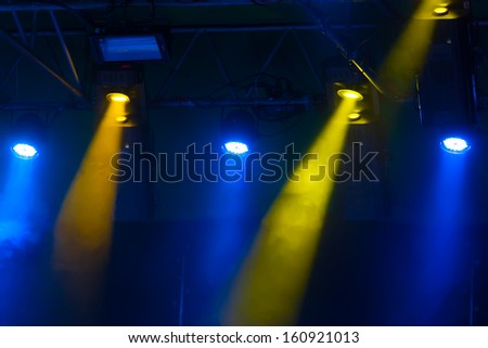 yellow and blue spotlights that illuminate the stage at a concert with fog