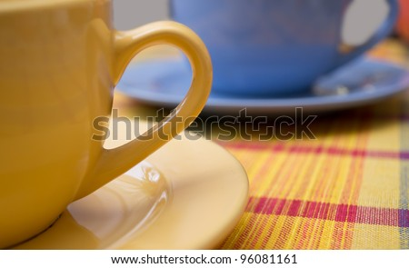 yellow and blue teacups on the table - stock photo
