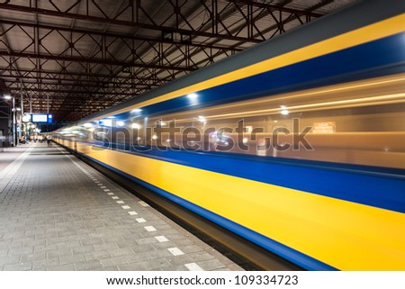 Yellow and blue train arriving in a big roofed dutch train station in the evening in the netherlands
