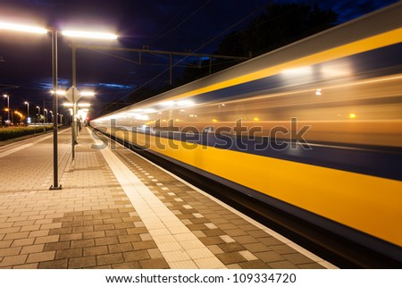 Yellow and blue train leaving a small roofless dutch train station at night in the netherlands - stock photo