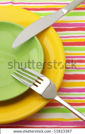 Yellow and green plates, stainless fork and knife on multicolored striped napkin. - stock photo