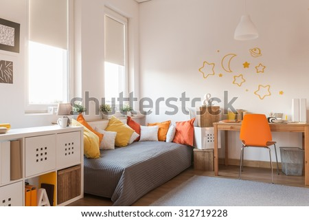 Yellow and orange accessories in modern teen room - stock photo