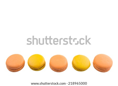 Yellow and orange colored French macarons on white background