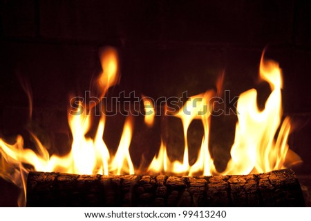 Yellow and orange flames and embers burning in a fireplace. - stock photo