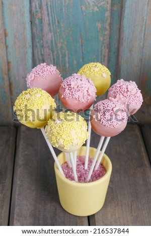 Yellow and pink cake pops on wooden background - stock photo