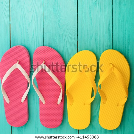 Yellow and pink flip flop sandals on blue wooden background. Top view and selective focus - stock photo