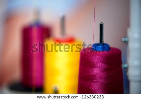 Yellow and pink reels of thread at tailor's