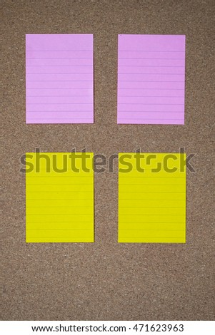 Yellow and pink  sticky note on cork board.