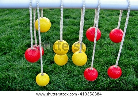 Yellow and red balls hanging on the ropes against green grass - stock photo