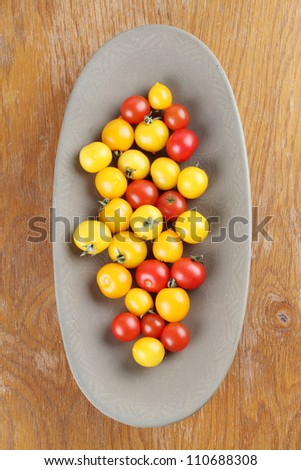 Yellow and red cherry tomatoes in a bowl. Shallow dof
