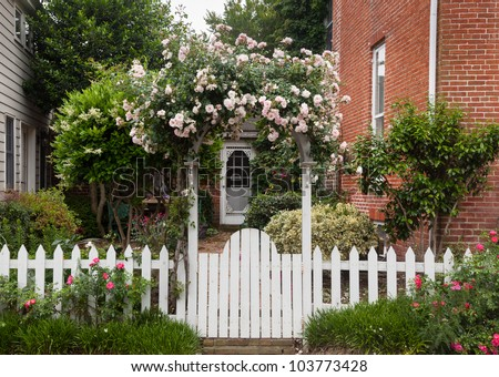 Yellow and red flowers growing along a white picket fence in traditional garden - stock photo