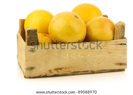 yellow and red grapefruit in a wooden box on a white background