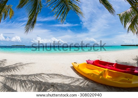 yellow and red kayak on the beach under coco palms - stock photo