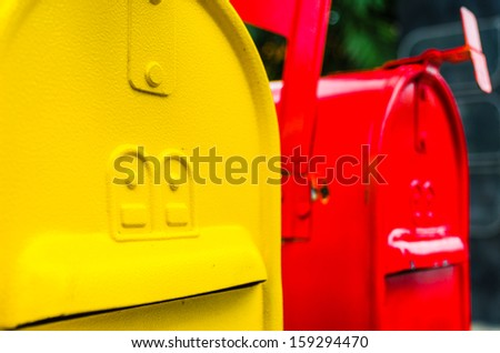 Yellow and red mailboxes - stock photo