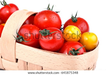 Yellow and red tomatoes lie in basket on a white background. Isolated.