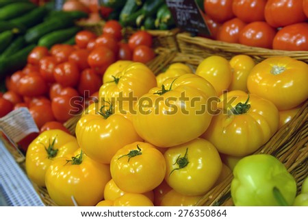 yellow and red tomatoes on display at a supermarket - stock photo