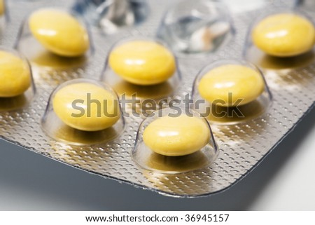 Yellow and round pills in a factory packing - stock photo