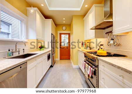 Yellow and white bright kitchen with skylight and grey floor. - stock photo