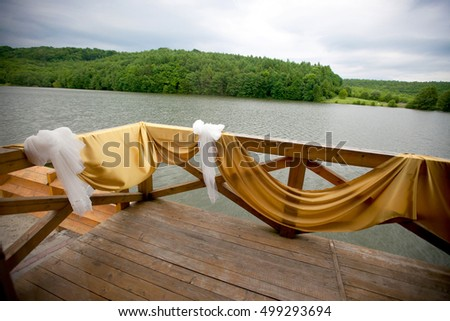 Yellow and white cloth decorated wooden porch over the river