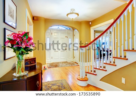 Yellow and white entrance hall with archway and spiral staircase - stock photo