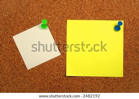 Yellow and white papers attached to a corkboard.