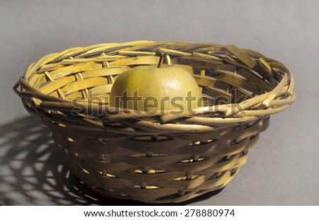 yellow aplle on yellow basket - stock photo